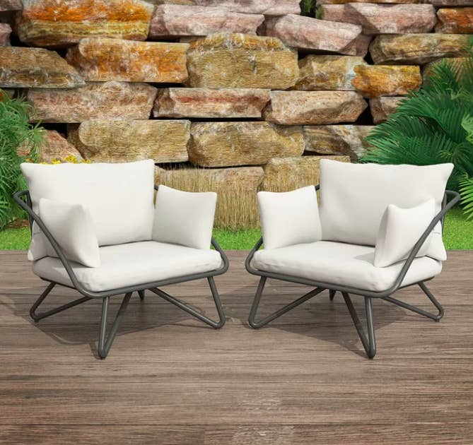 White plush patio chairs with charcoal-colored legs on a deck near a garden wall