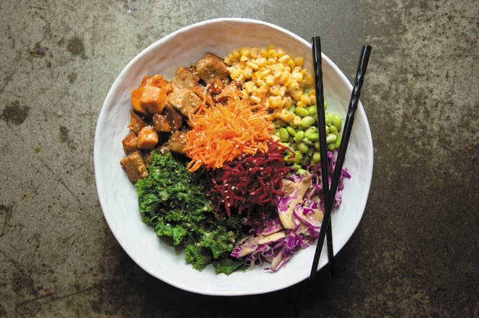 A plate featuring tofu, carrots, beets, cabbage, corn, edamame, and kale.