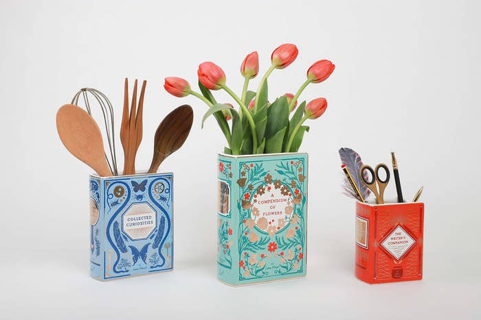 Three different designs of the book vase, containing flowers, kitchen utensils, and stationery.