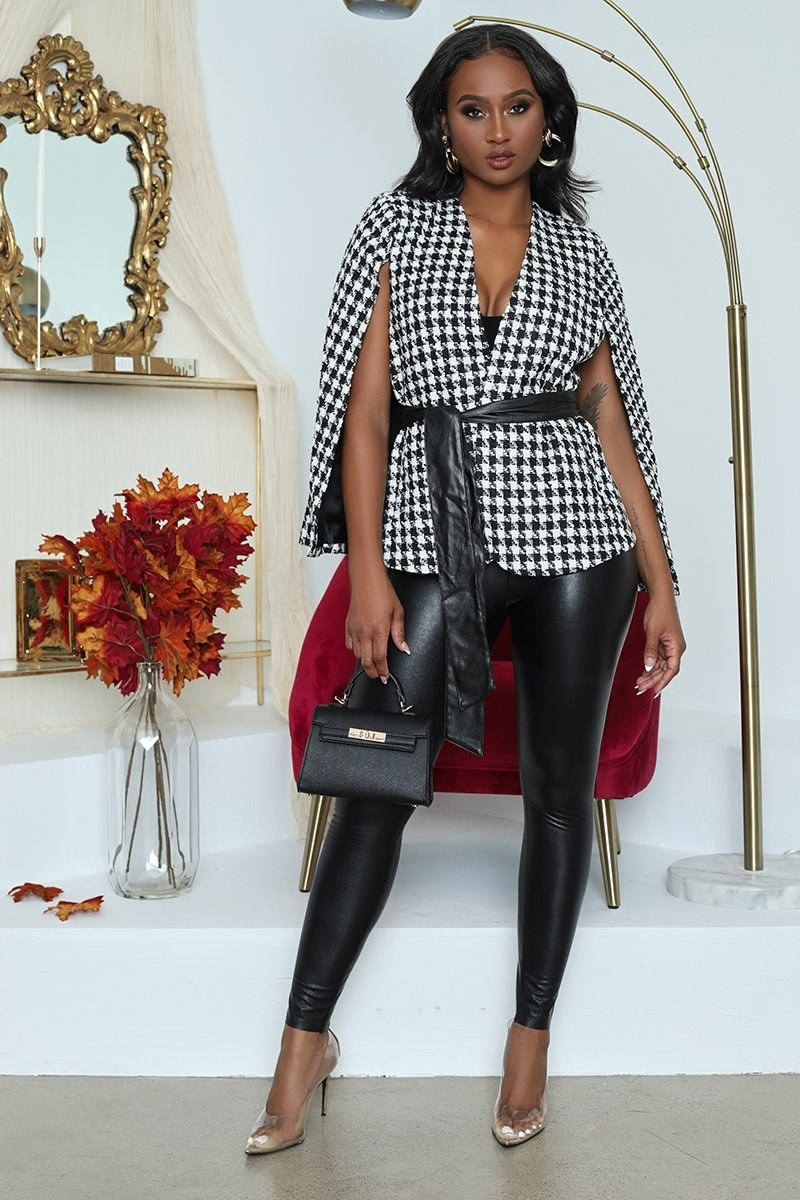 Model wearing the blazer-style jacket with a cape on the back, black and white houndstooth pattern and a wide faux-leather belt around the waist