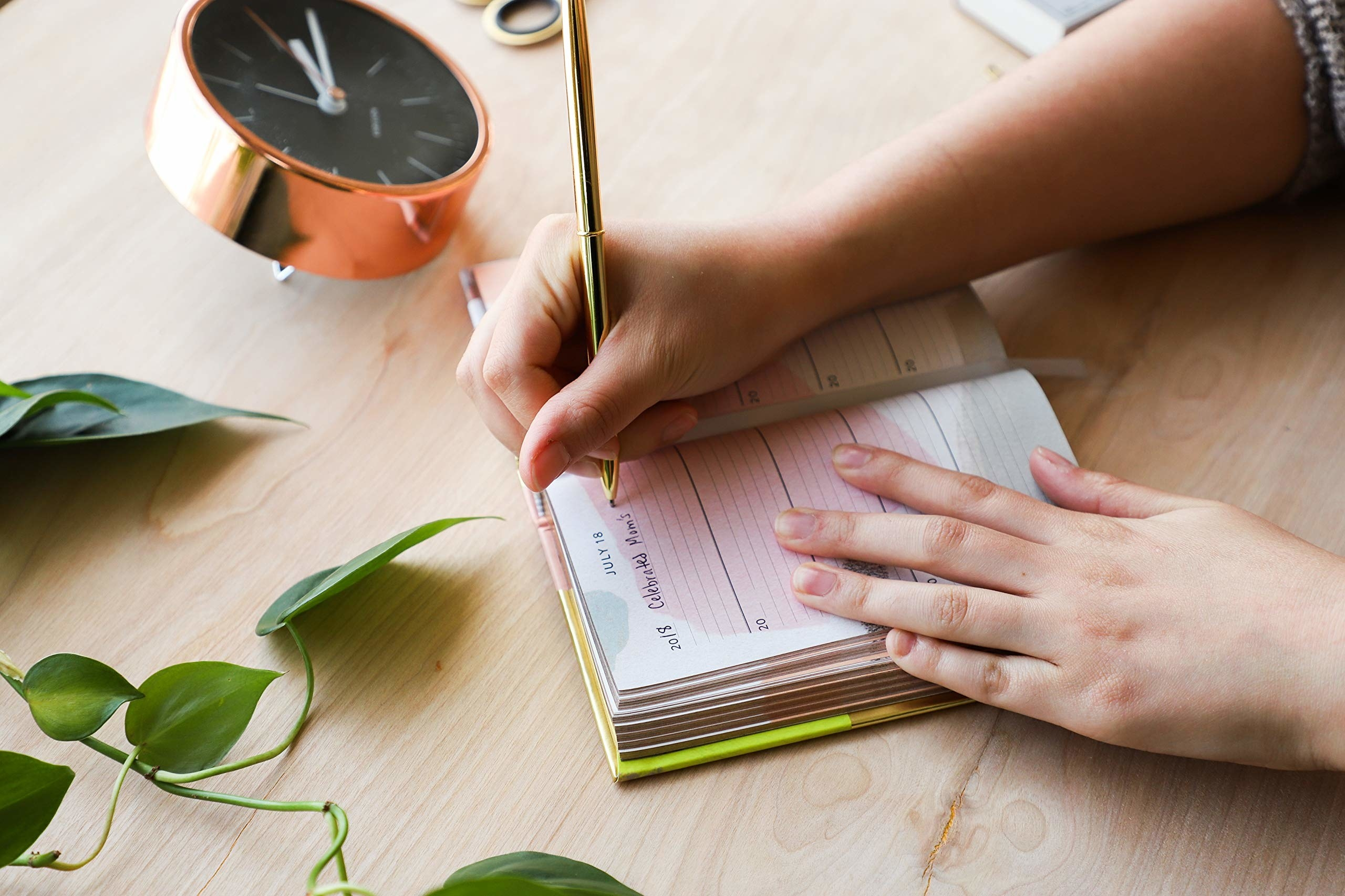 """A hand writing """"Celebrated Mom's..."""" in the notebook."""