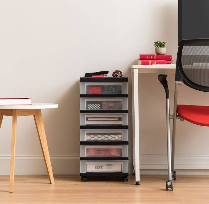 Freestanding clear plastic drawers with a black frame on caster wheels