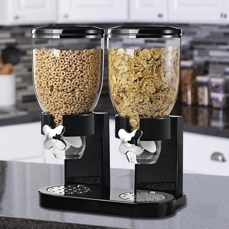 the black dispenser with two glass lids filled with cereal