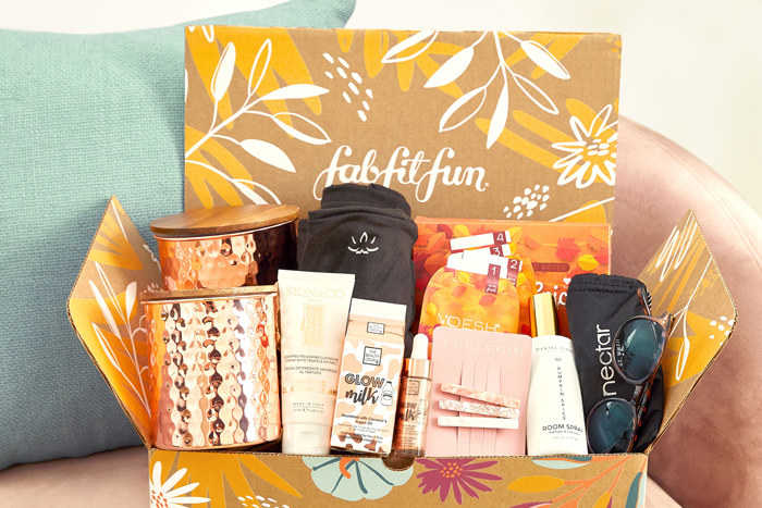 a box filled with candles, hair products, sunglasses, etc