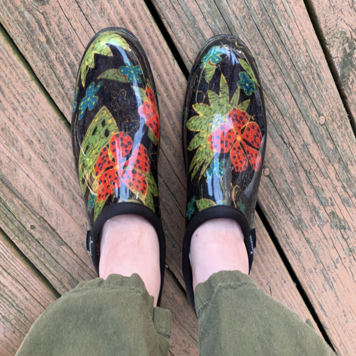 a reviewer wearing the rubberized, clog-like shoes with a floral pattern on them