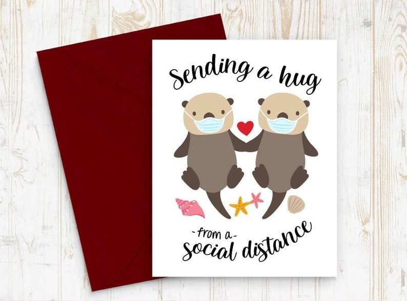 "A card with two little creatures wearing masks that says ""Sending a hug from a social distance."""