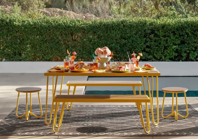 Yellow picnic table and stool set covered with margarita drinks and snacks on a patio