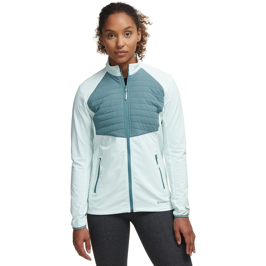 Model wearing the zip-up jacket in a light blue with a darker blue insulated section on the chest and vertical zip pockets on each side