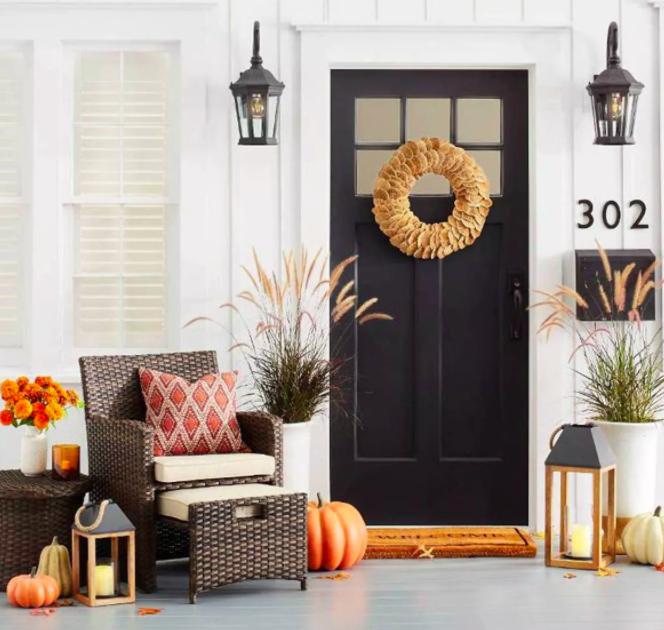 Rope and wood lantern next to orange pumpkins and dark brown patio furniture