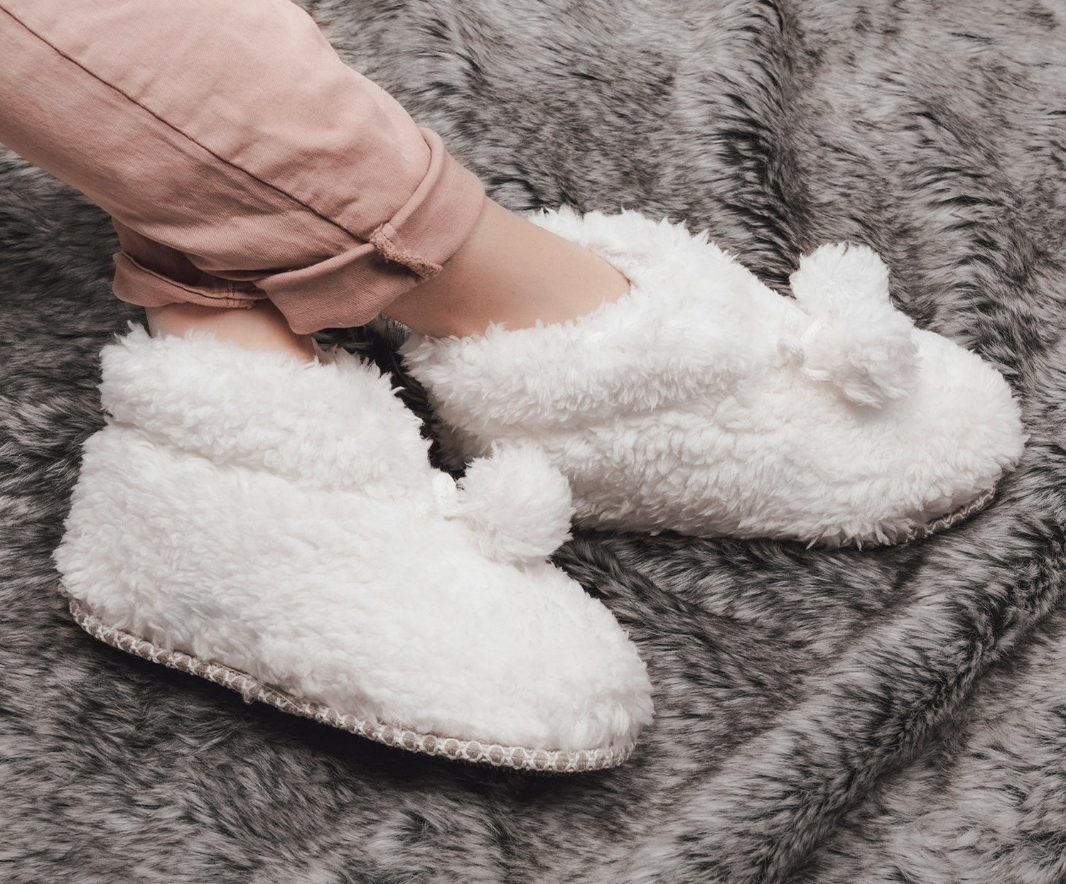 A pair of ivory faux fur bootie slippers on a model's feet