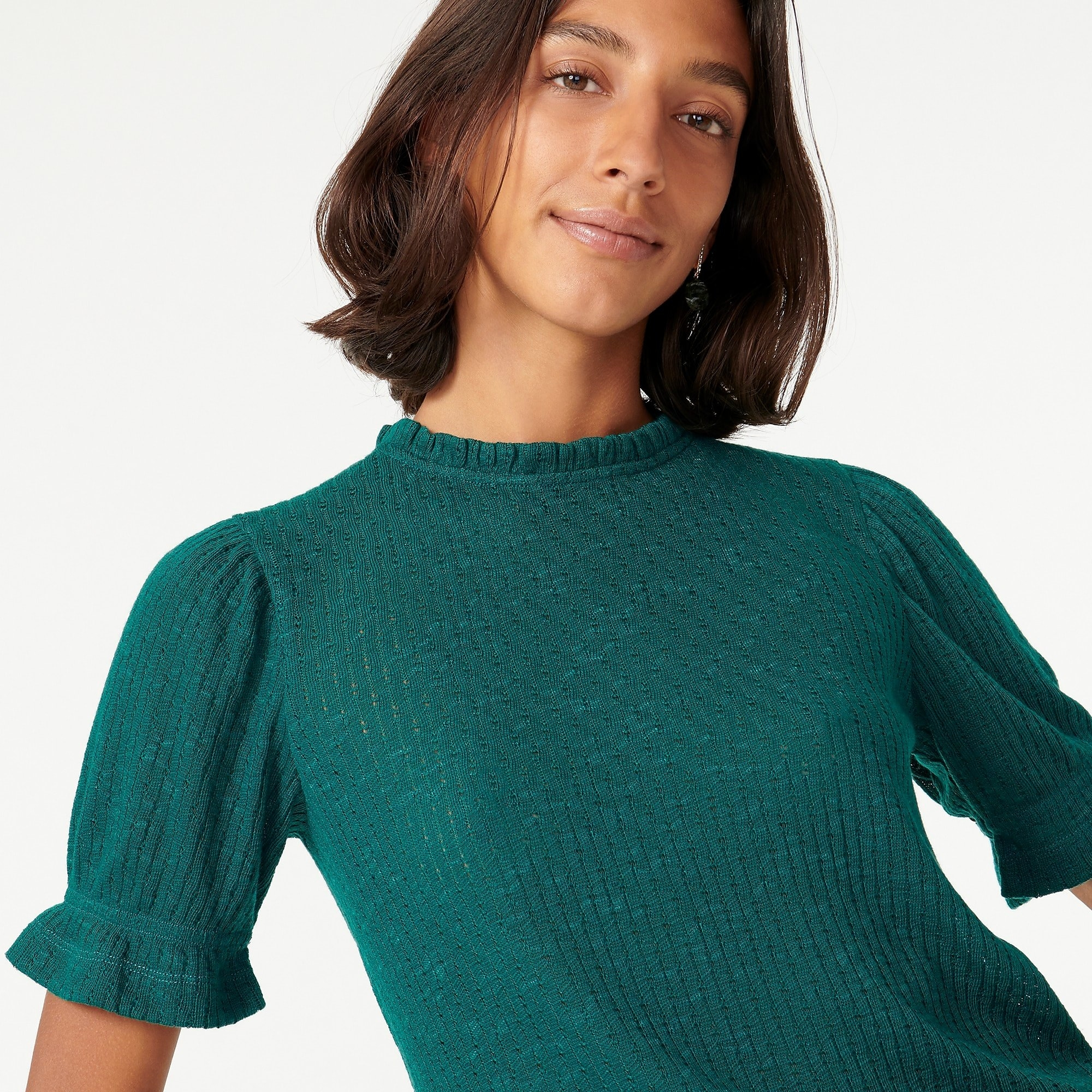 model wearing teal green sweater pointelle top with ruffle at neckline and puff sleeve
