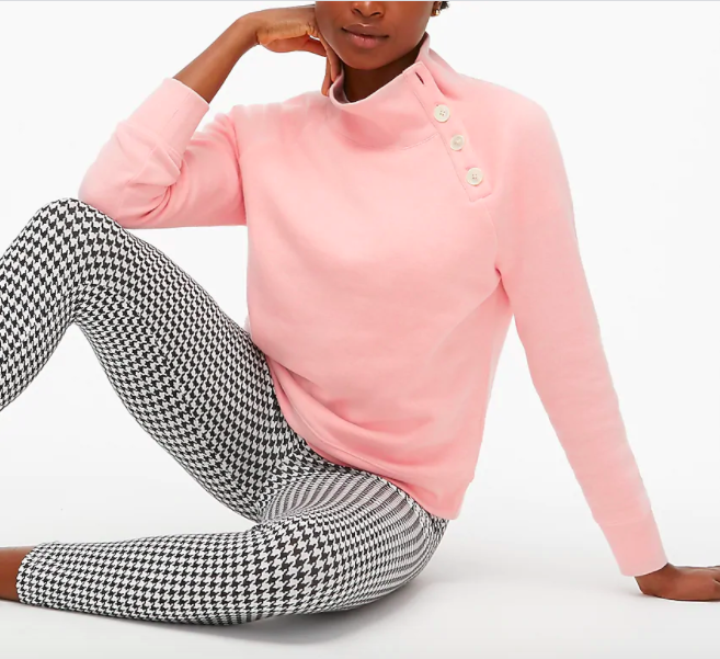 model wearing light pink sweatshirt with high neck that has button detail on one side