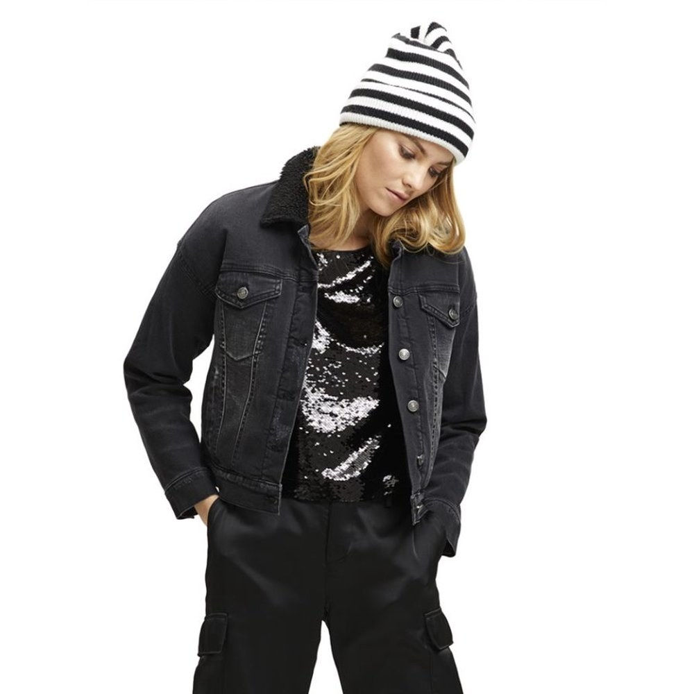 Model wearing the black denim jacket with a fuzzy sherpa lining, buttons down the front and pockets on each side of the chest.