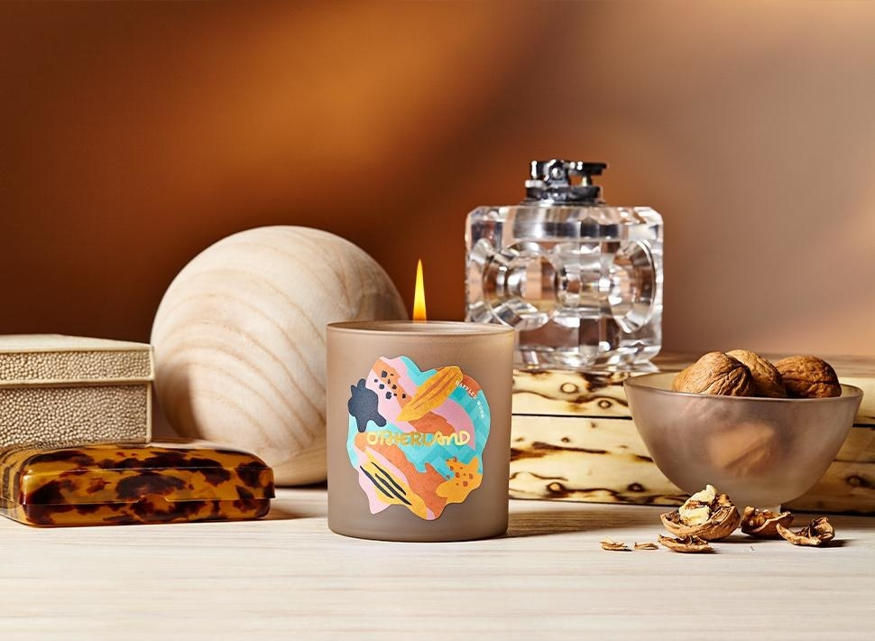 The dappled wood candle is in a brown frosted glass with a colorful Otherland logo on the front