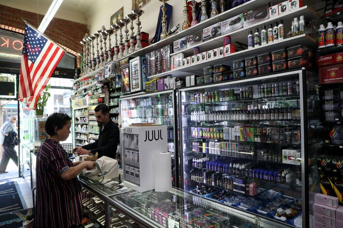 A customer talks to a cashier at a vape shop in San Francisco, surrounded by vapes and vaping liquid supplies