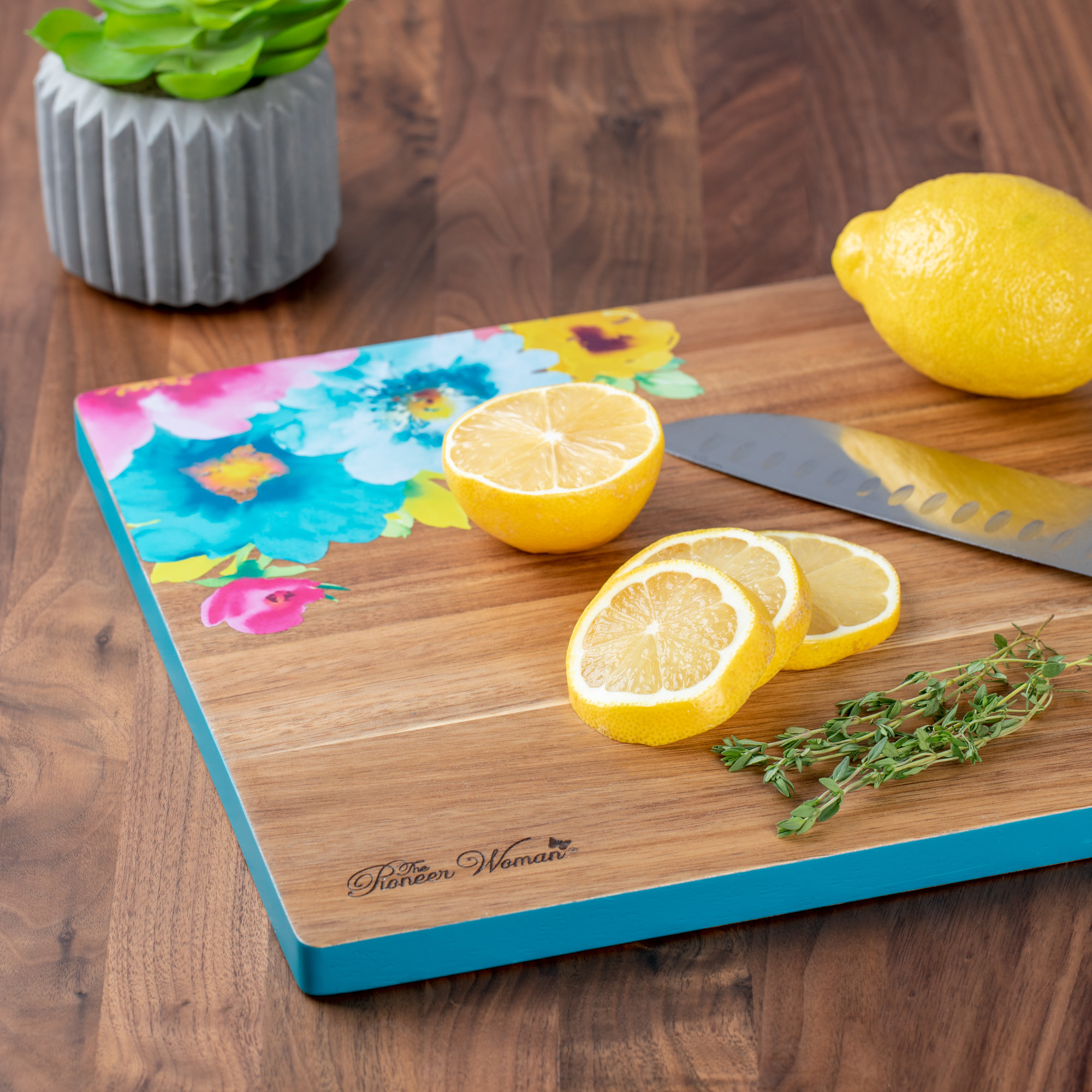 A wooden cutting board with teal edges and teal, pink, and yellow flowers drawn on the surface