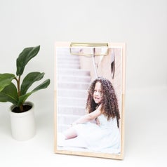clipboard made of thick wood and displaying the photo of a little girl and sitting beside a small plant.