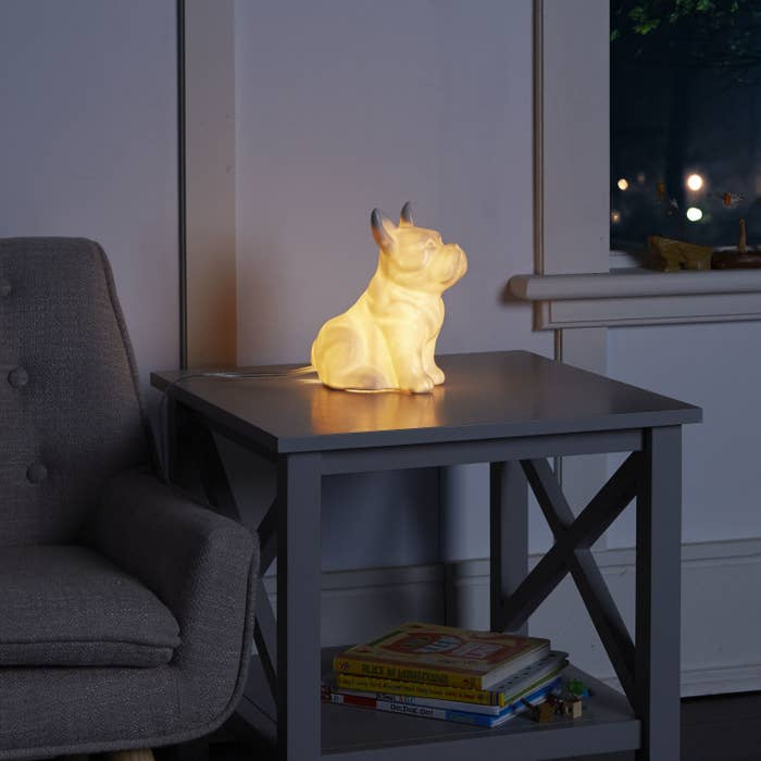 A lit french bulldog lamp sitting on an end table