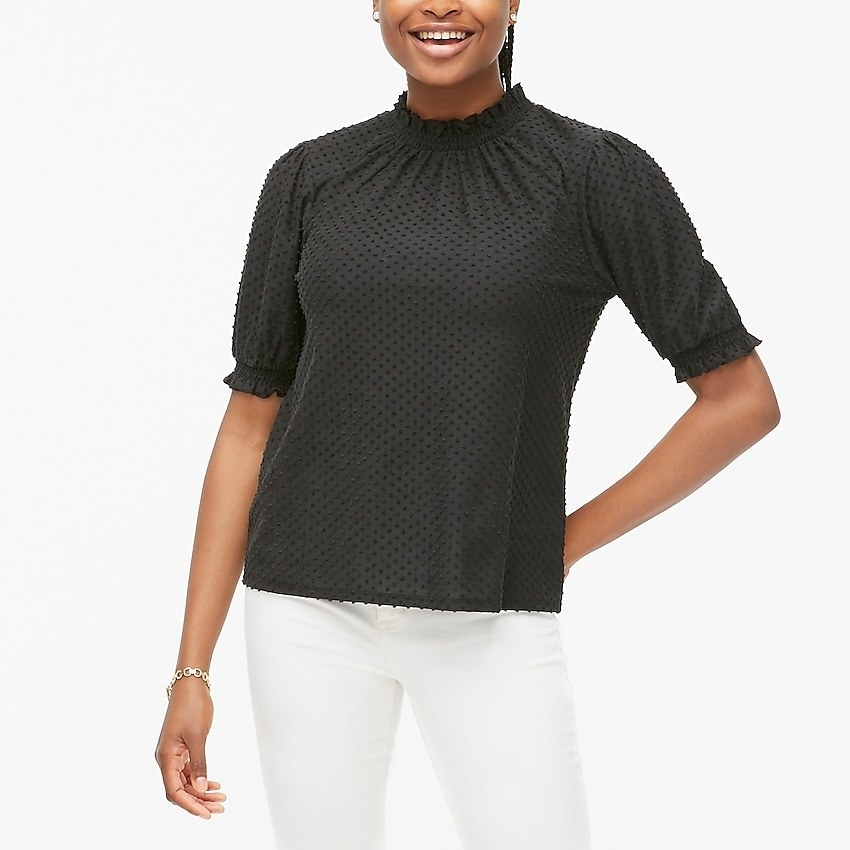 Black top with ruffled quarter-length sleeves, high collar, and polka dot thread pattern