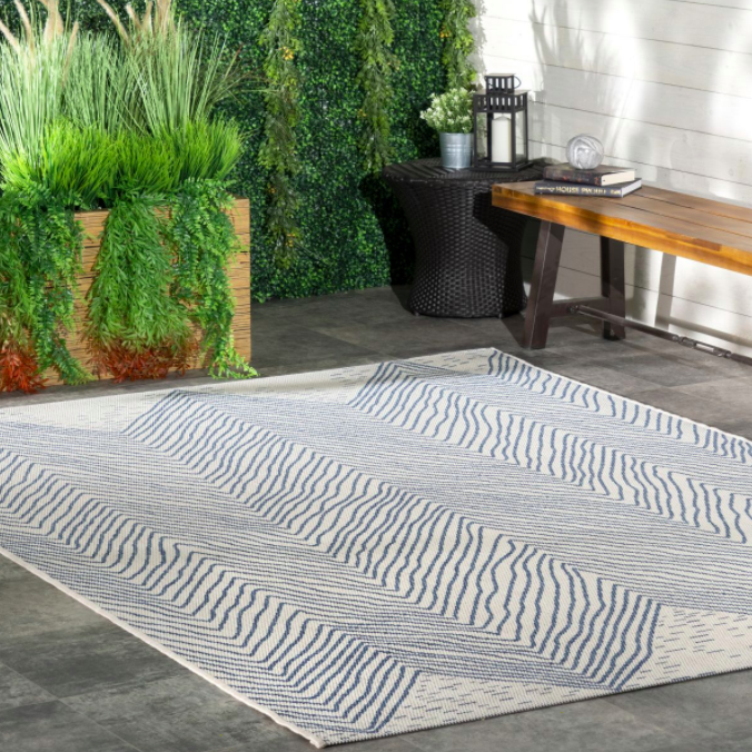 Blue and white chevron-patterned rectangle rug next to plant and outdoor bench
