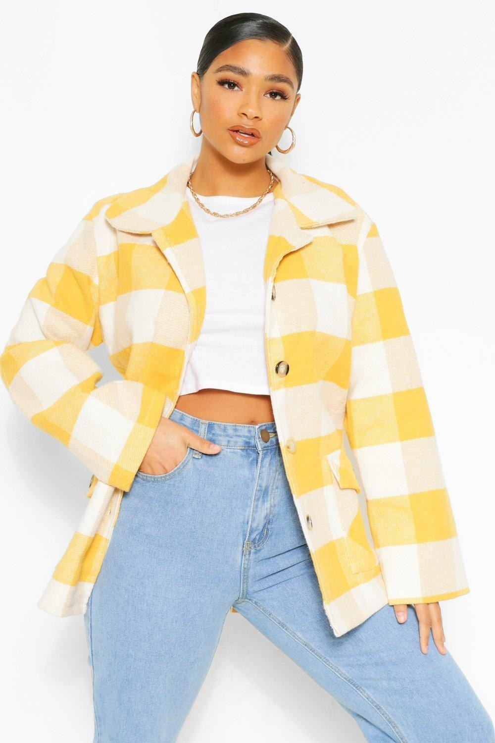 Model wearing the button-front coat with a yellow plaid pattern and oversized collar