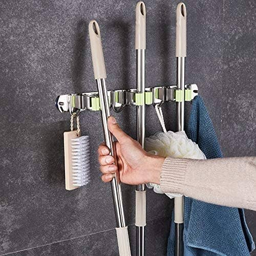 A person pulling a long-handle broom off a wall mounted hook