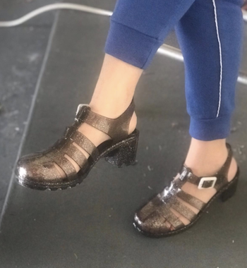 a reviewer in the black glittery heeled jelly shoes