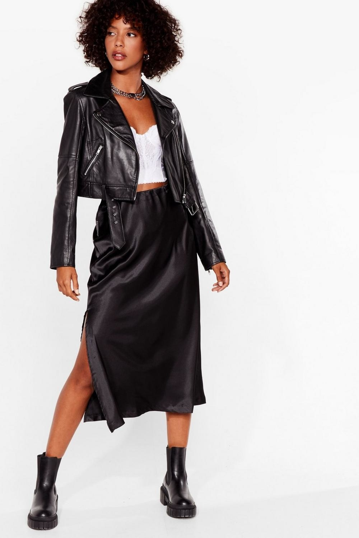 Model wearing black silky midi, showing high side slit