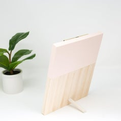 the back of the clipboard display which has an angled wooden stick at the bottom to make it stand up like a photo frame would