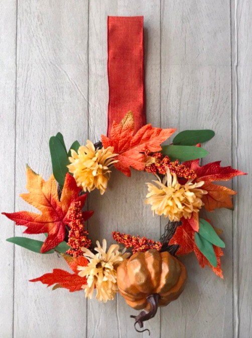 Mini fall wreath adorned with red and orange leaves, a pumpkin, and dried flowers
