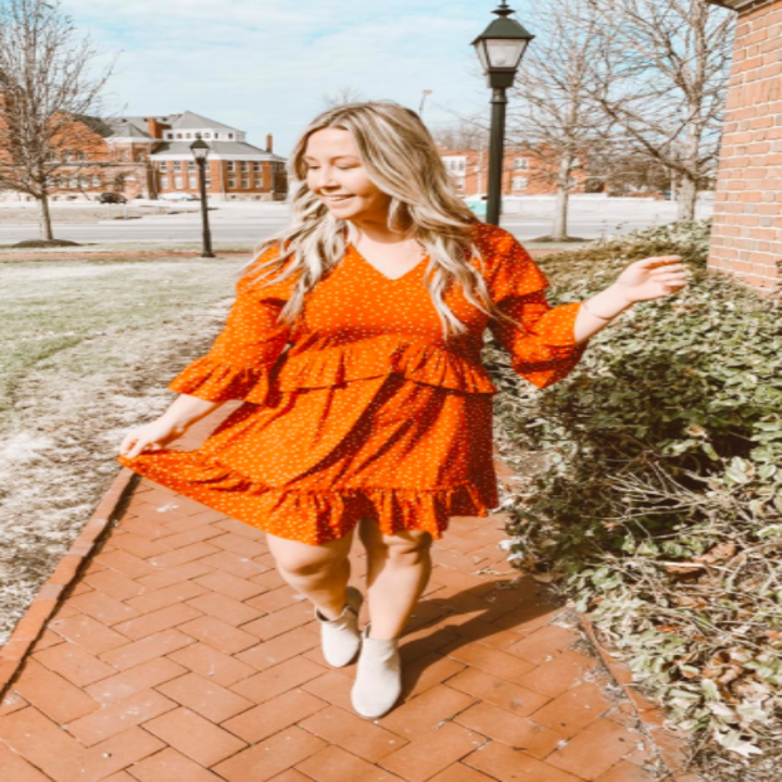 A reviewer wearing the dress in orange with white polka dots with taupe booties