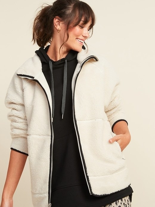 Model wearing the white fuzzy jacket with black trip, zipper up the front, and large pockets on the sides.
