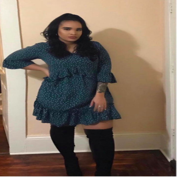 A reviewer wearing the three quarter-sleeve dress in teal with white polka dots with black thigh-high boots