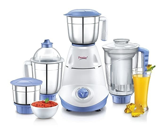The grinder with the three different grinding jars and the juicing jar, along with a bowl of chutney and a glass of juice on each side.