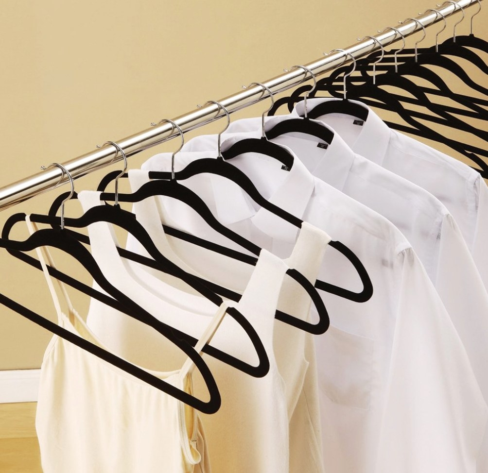The black hangers holding white collared shirts and tank tops