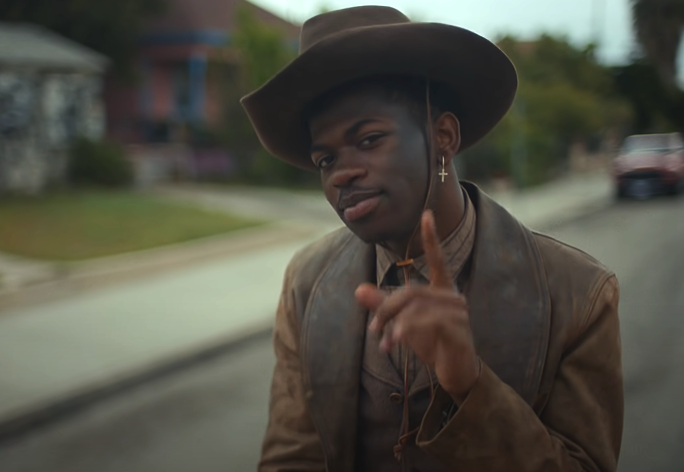 Lil Nas X riding on a horse down an empty road while wearing a cowboy hat