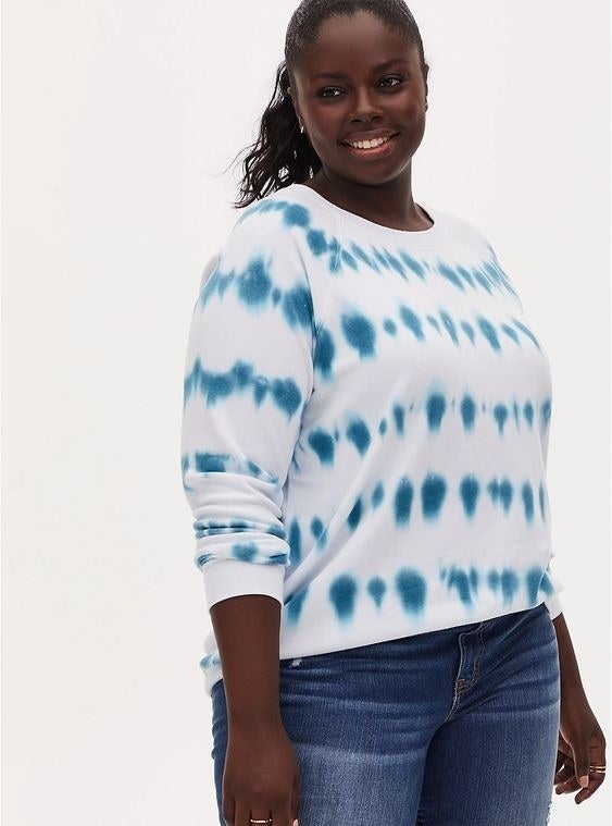 Model wearing the blue and white crew-neck sweatshirt