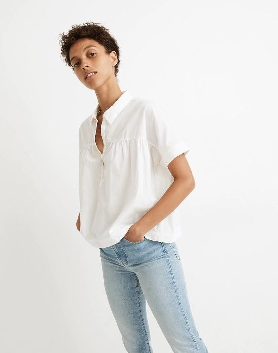 Model wearing the white short sleeved blouse