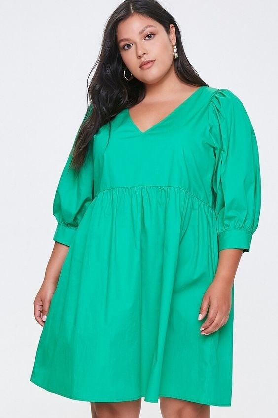 Model wearing the three quarter-length sleeved dress in green