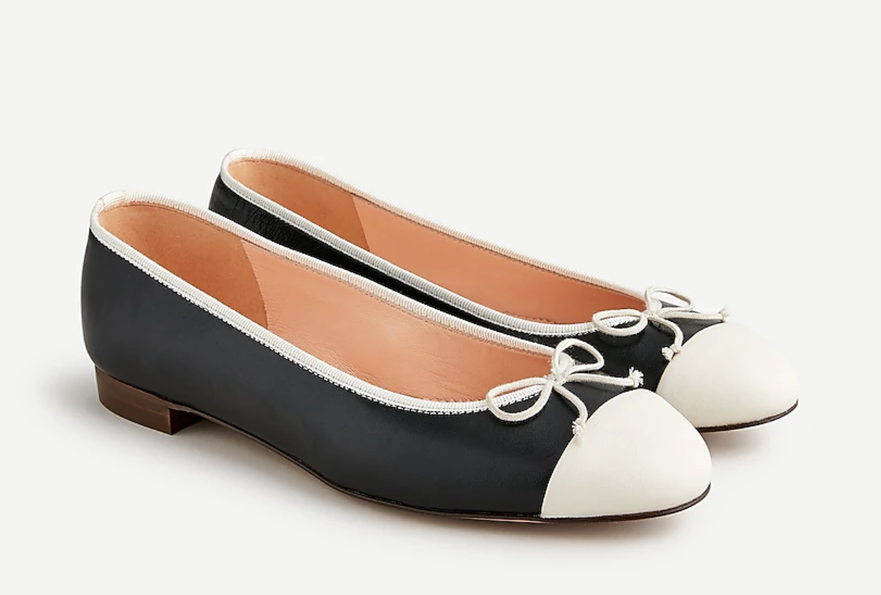 black flat shoes with ivory accents and a small bow