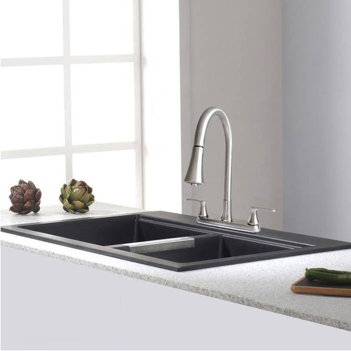 A brushed nickel kitchen faucet with a pull-down spray installed on a sink in a kitchen