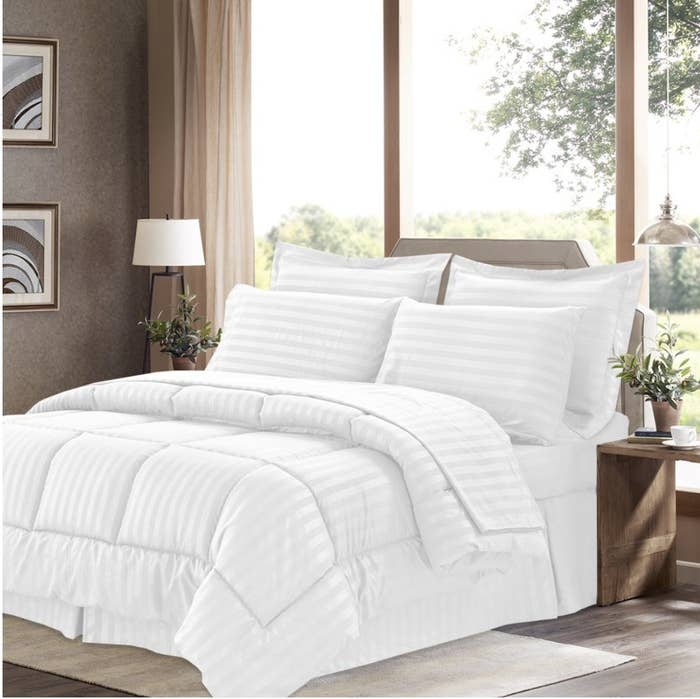 A white eight-piece comforter set on a bed with four pillows in a bedroom
