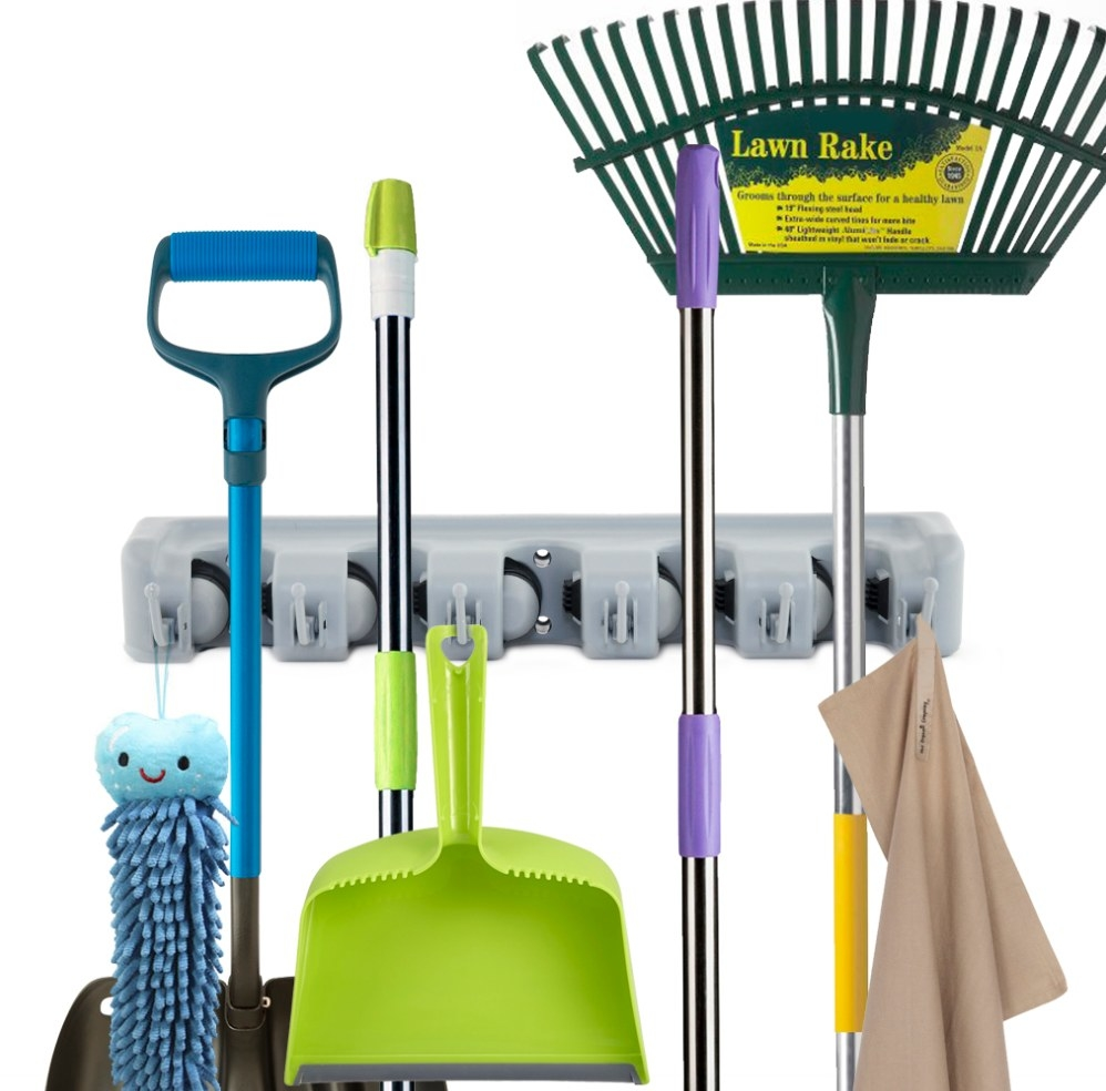 The gray wall holder being used to hold a rake, broom, and dustpan