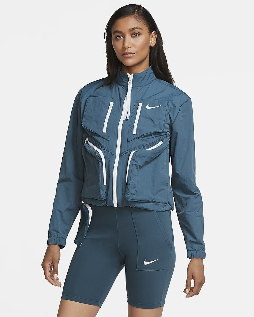 The woven jacket in blue with four pockets on the front with bright white zippers and a white zipper up the front.