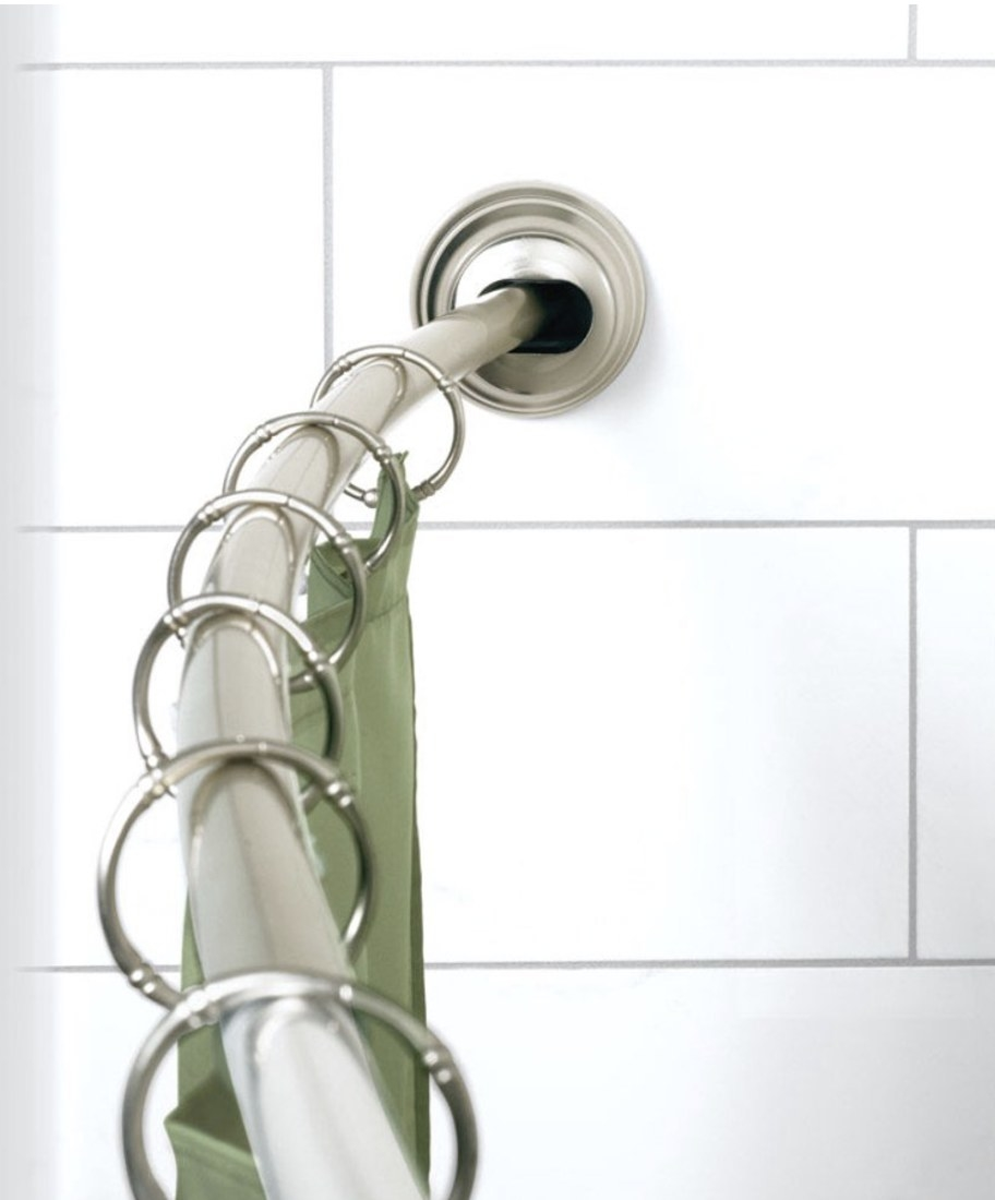 A closeup of a curved chrome shower rod installed on bathroom tile with hooks and a shower curtain hanging