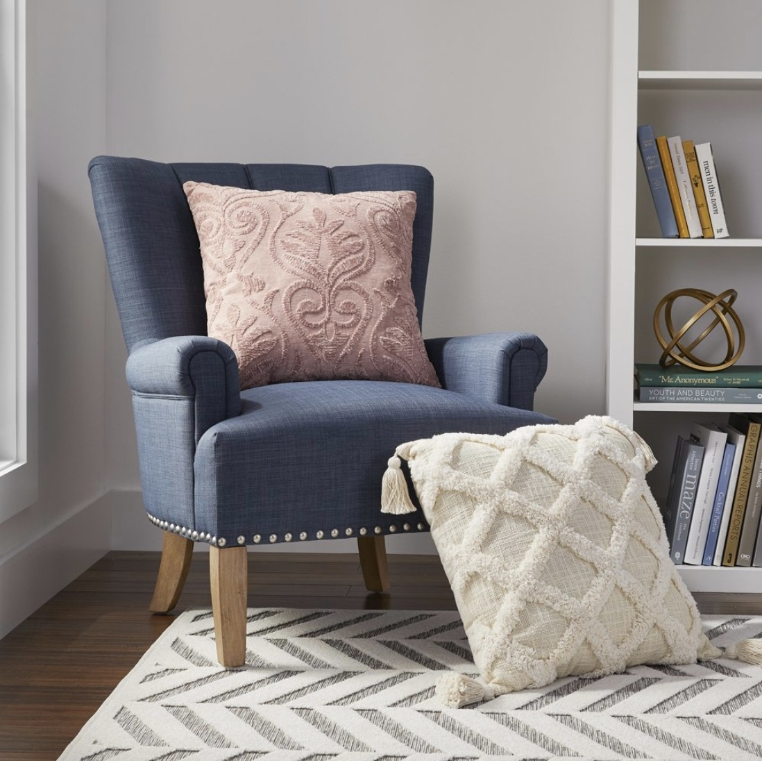 A cream textured throw pillow on the floor with tassels attached to each corner and a pink textured throw pillow on a blue chair