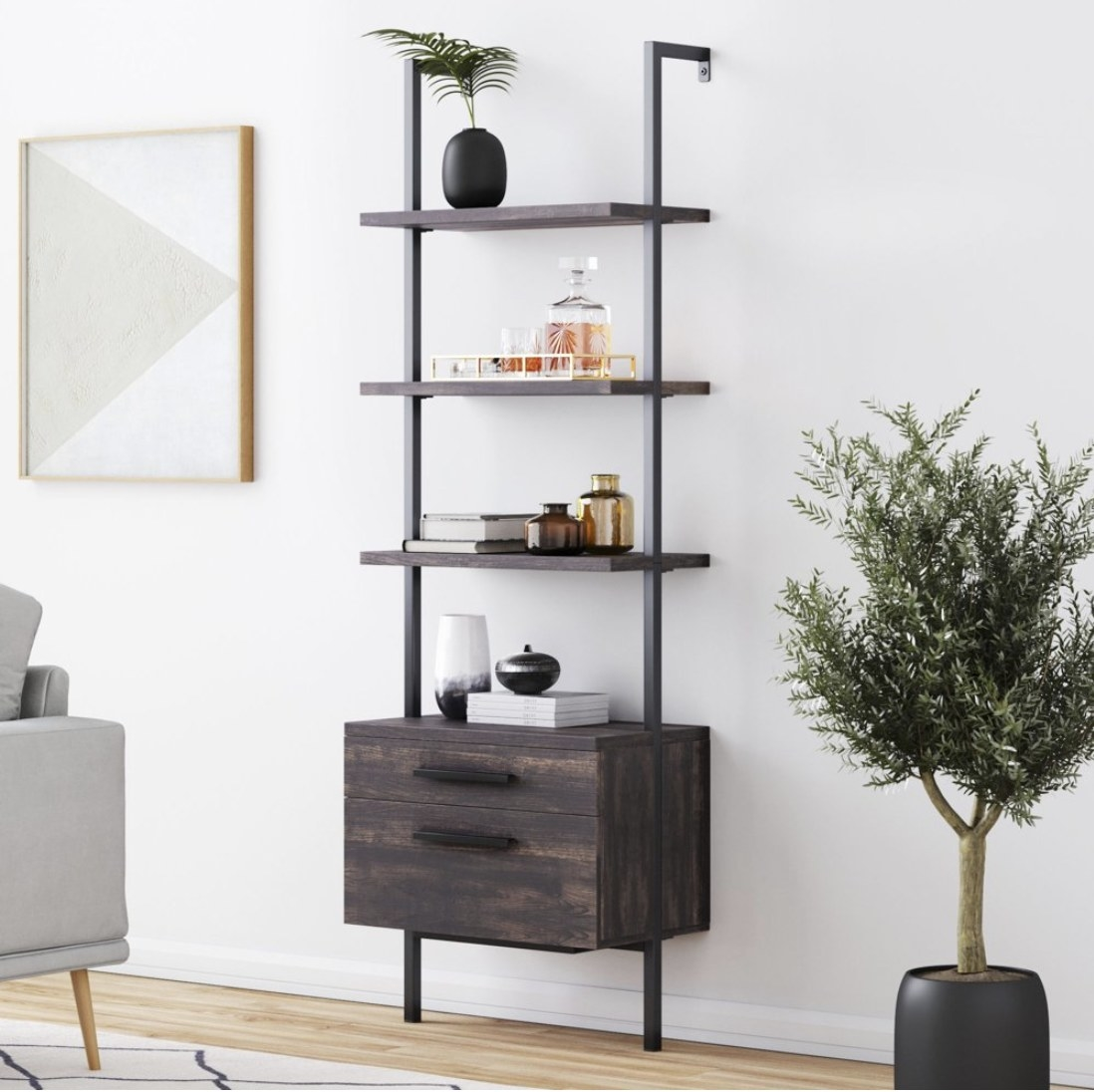 An industrial-style bookshelf with two drawers on the bottom and open shelves on the top mounted to the wall of a living room