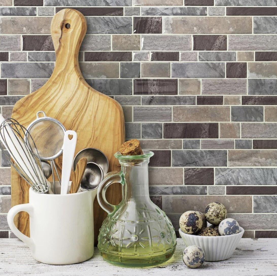 Peel and stick stone backsplash of various grey tones with kitchen products propped in front of it