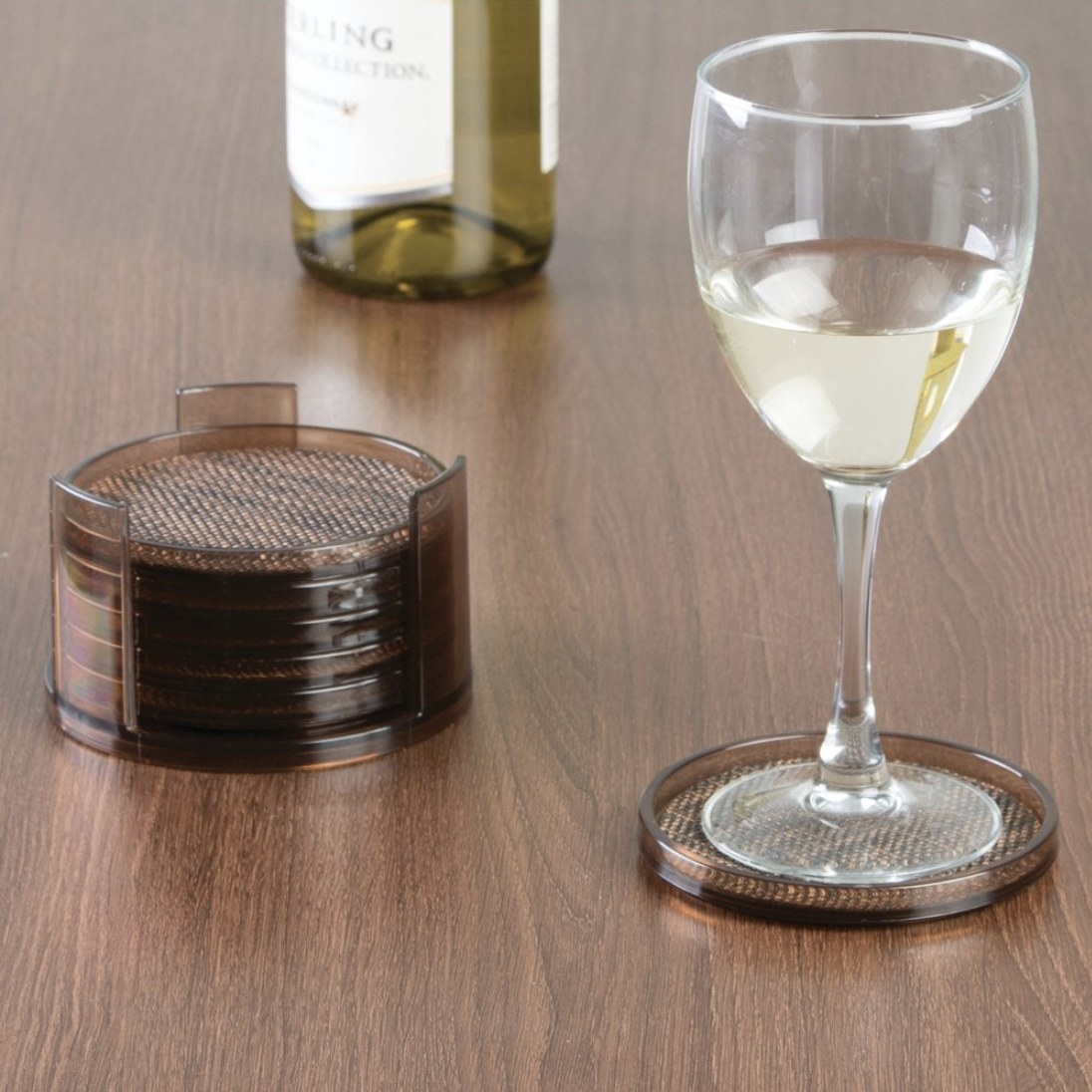 A set of coasters in a stack and one on a table under a wine glass filled with white wine