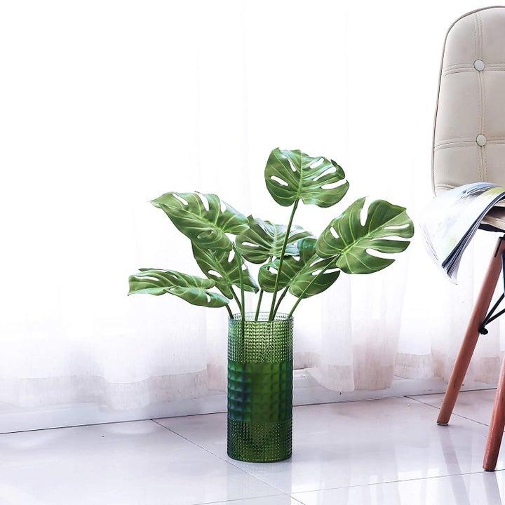 Bushel of faux monstera stems in a green vase